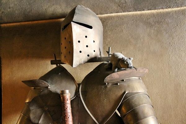 a suit of armor with a fake rat sitting on the shoulder