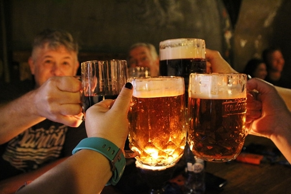 4 glasses of beer clicking each other over a table