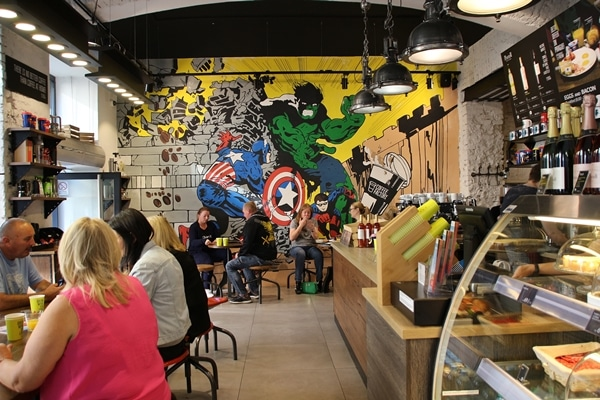 interior of a cafe with superheros painted on the far wall