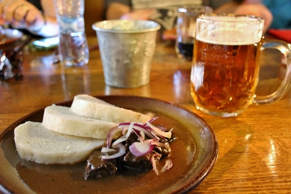 a plate of beef goulash next to a glass of beer