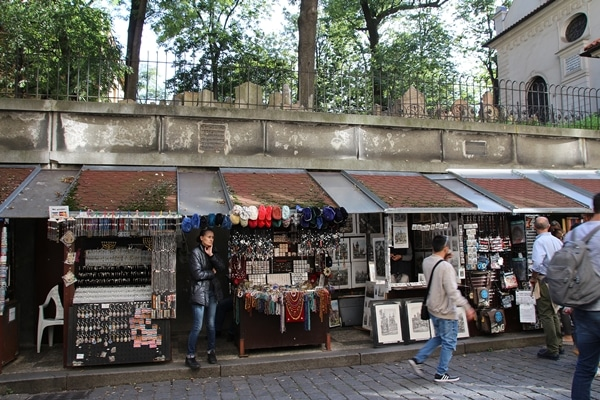 small shops on a street beneath a cemetery