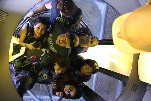 view of a group of people in an elevator, captured in a mirrored ceiling