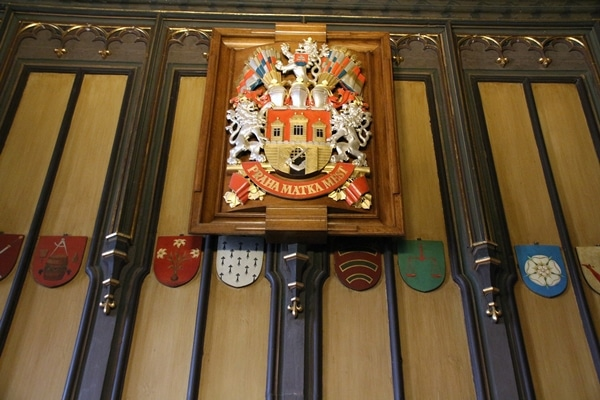 ornate decorations, emblem and wood paneling on a wall