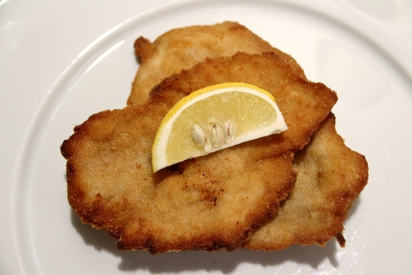 2 pieces of fried pork schnitzel with a lemon wedge