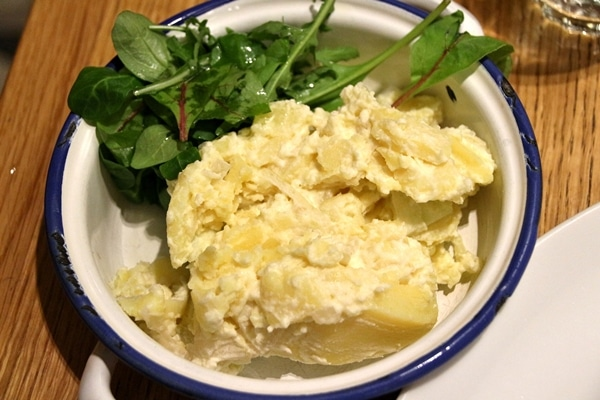 potato salad with a side of greens in a wide bowl