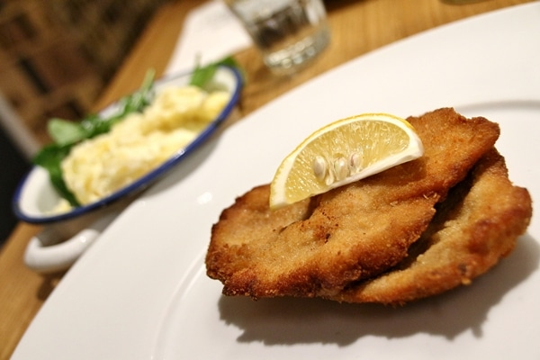 a plate of schnitzel with potato salad in the background