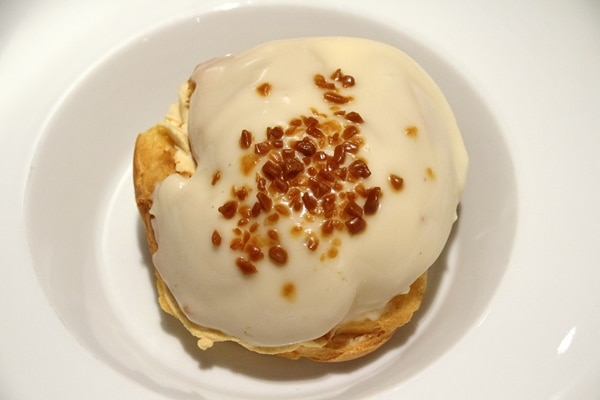 overhead view of a caramel profiterole on a white dish