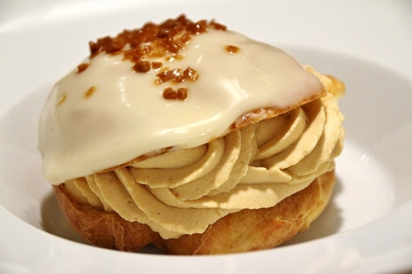 side view of a caramel profiterole on a white plate
