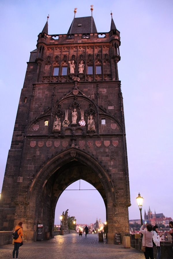 A large stone tower at the end of a bridge at dawn
