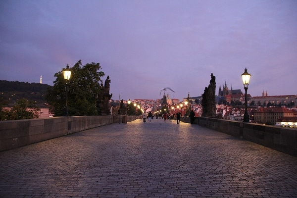 A nearly empty Charles Bridge in Prague at dawn