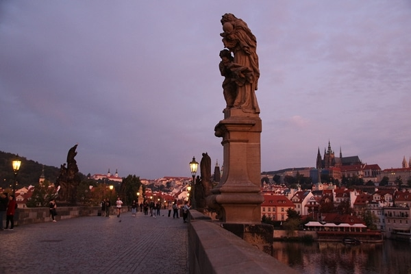 statues on nearly empty Charles Bridge at dawn
