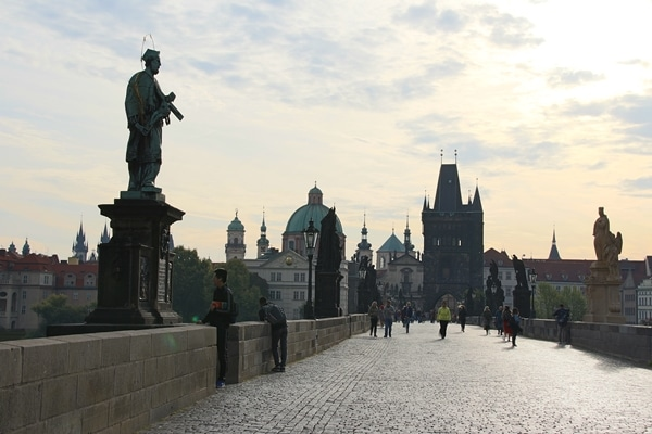 a morning view of mostly empty Charles Bridge in Prague