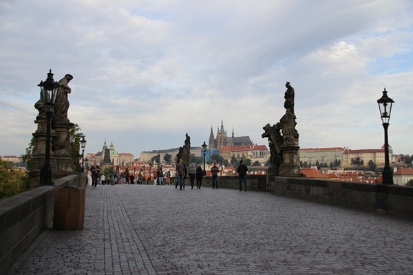 view of statues and Prague Castle from nearly empty Charles Bridge