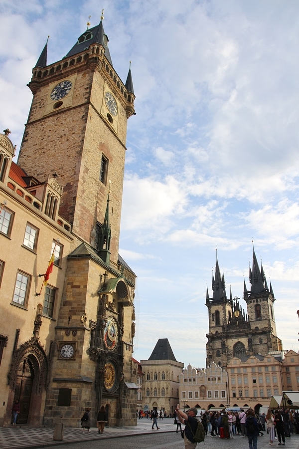 morning in a Prague square with a large clock tower and church