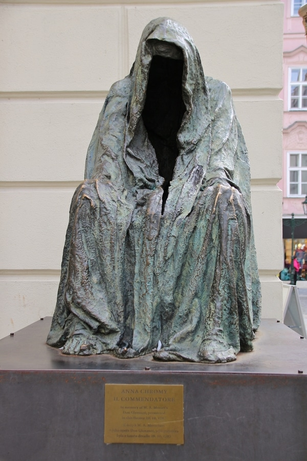 a metal statue of a cloaked man