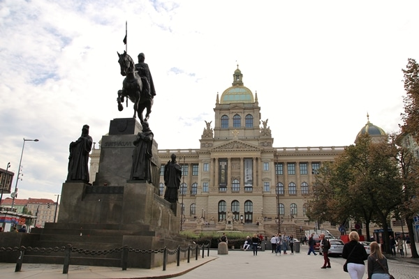 a statue of a man on a horse in front of a large building