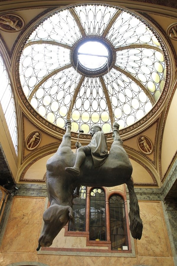 hanging statue of a man on an upside down horse