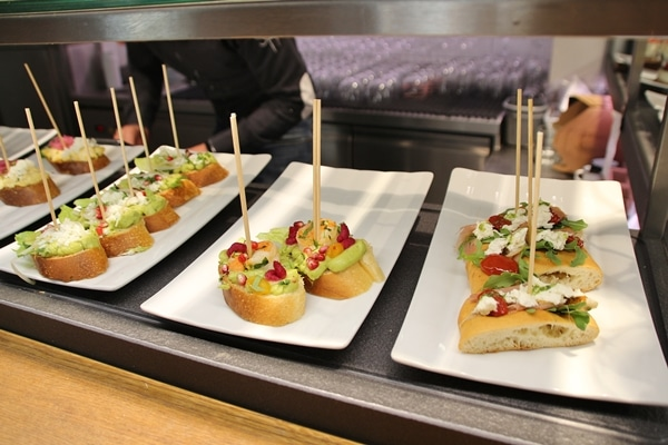 plates of open-faced sandwiches with skewers in them