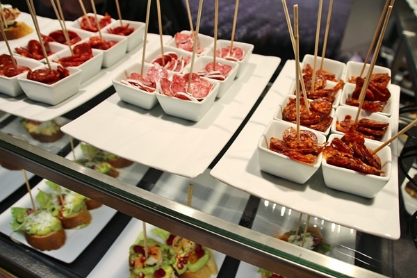 small dishes of food with skewers in them