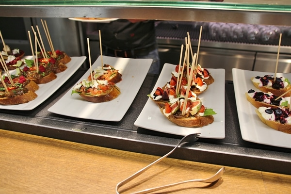 a buffet of open-faced sandwiches with skewers in them