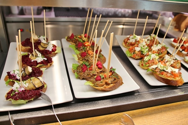 open-faced sandwiches on white plates with skewers sticking out