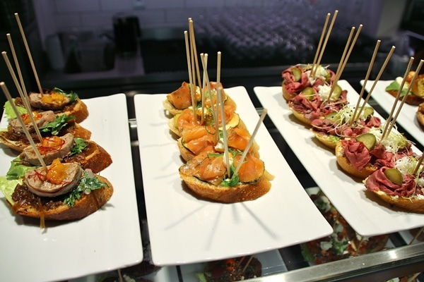 open-faced sandwiches on white plates with skewers sticking out of the tops