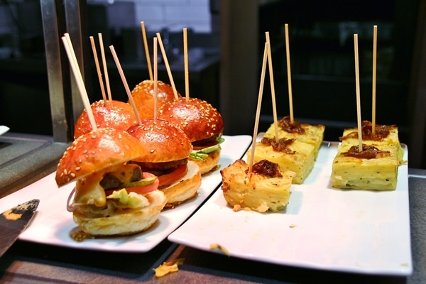 small burgers and other foods skewered with wooden sticks