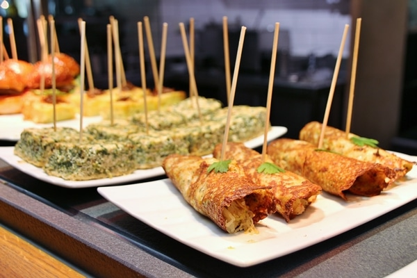 a buffet of various foods skewered with wooden sticks