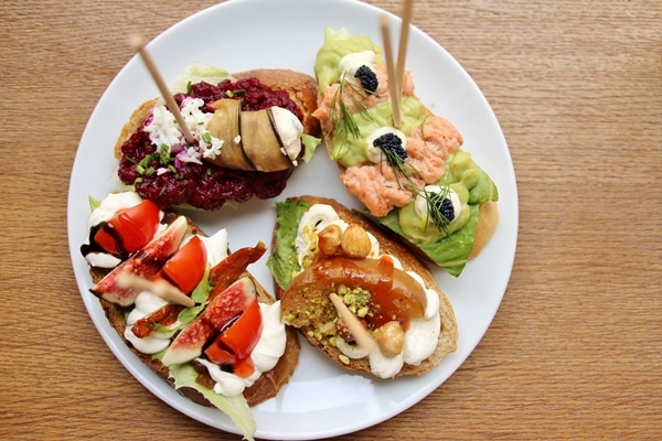 4 open-faced sandwiches on a white plate