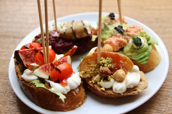 side view of 4 open-faced sandwiches with wooden skewers stuck in them
