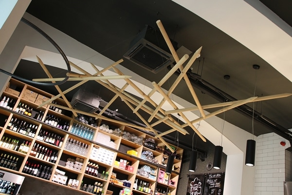 the interior of a restaurant with giant wooden skewers hanging from the ceiling