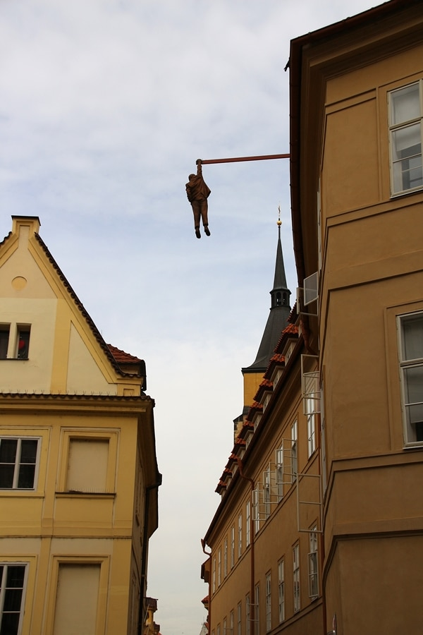 a statue of a man hanging from a building