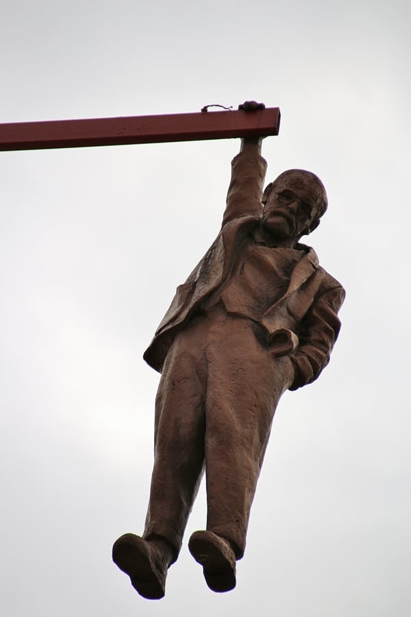 a statue of a man hanging from a pole
