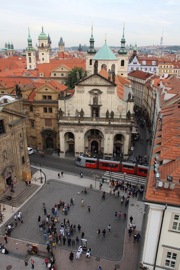 an overhead view of a Prague square with a tram running through it