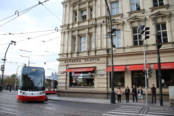 a tram driving by a corner building