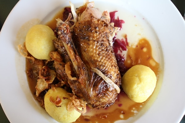 a plate of duck surrounded by potato dumplings