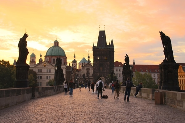 A group of people walking on Charles Bridge at sunrise