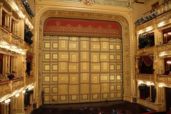 a gold curtain hiding the stage in an opera house