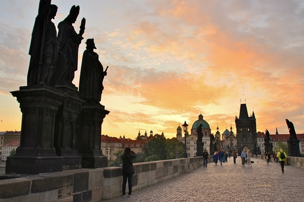 A group of people on the Charles Bridge at dawn