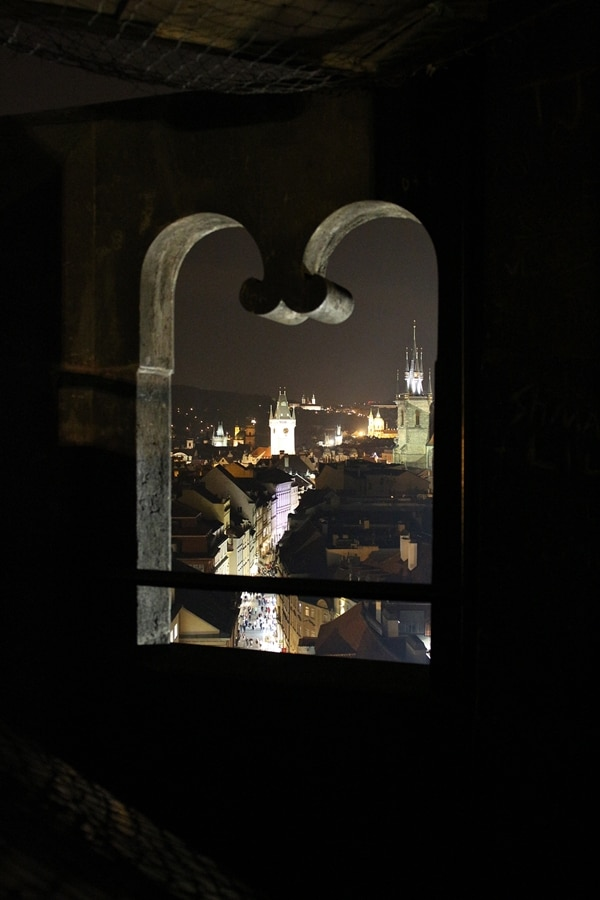 nighttime view of Prague through a window opening