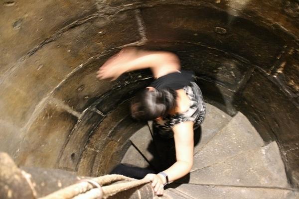 a woman walking down a spiral stone staircase