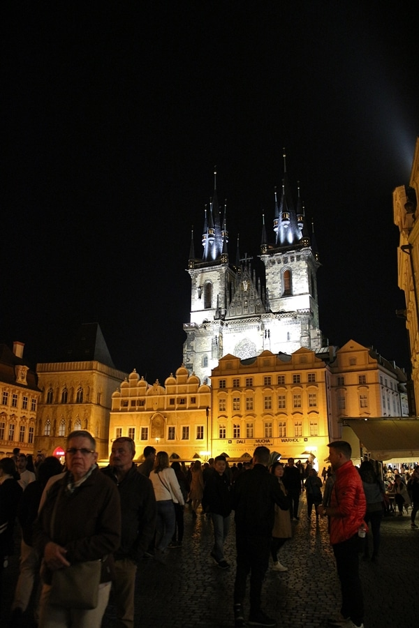 a group of people in a square at night in front of a large church
