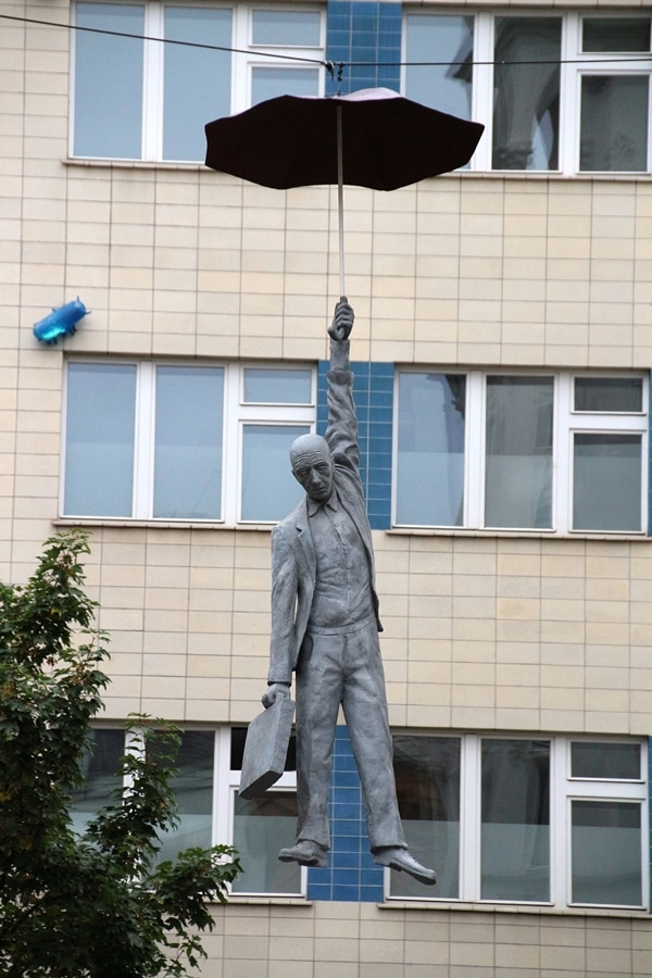 a statue of a man hanging from an umbrella