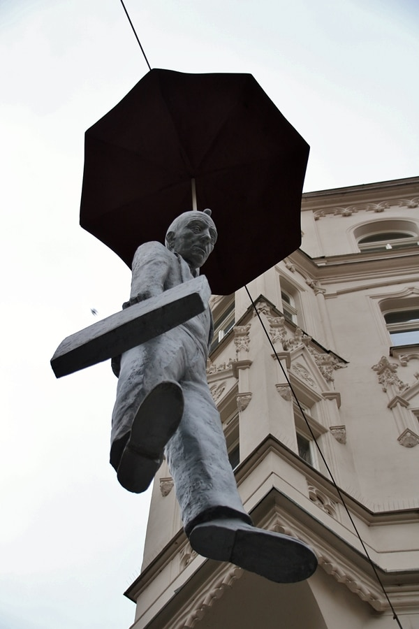 view looking up at a statue of a man hanging from an umbrella
