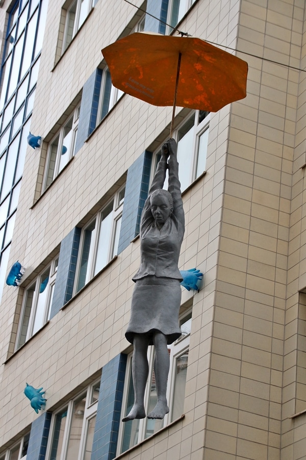 statue of a woman hanging from an umbrella