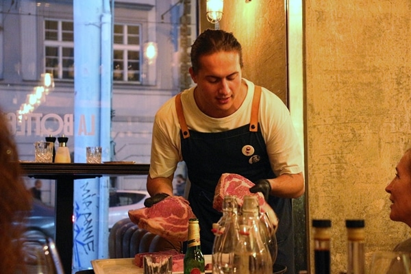 A man holding 2 large cuts of beef