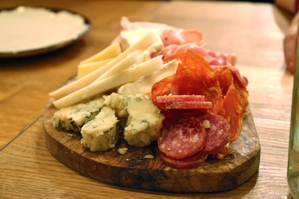 closeup of cured meats and cheeses on a wooden board
