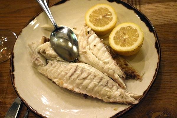 a fish fillet with lemon halves on a plate