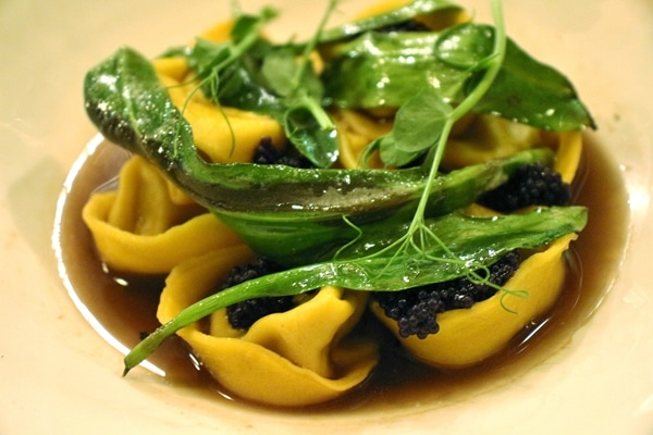 closeup of tortellini pasta with caviar and greens