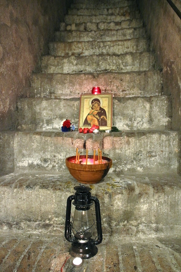 candles and a religious photo on stone steps